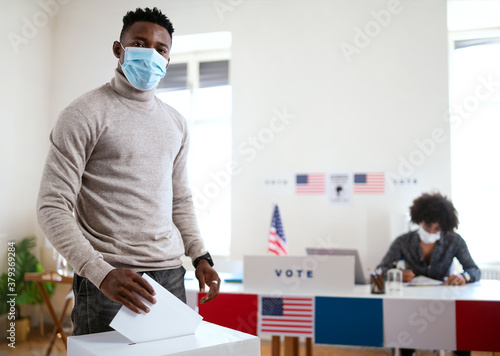 African-american man putting his vote in the ballot box, usa elections and coronavirus.