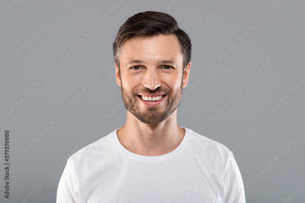 Fototapeta Handsome young caucasian man smiling at camera on grey