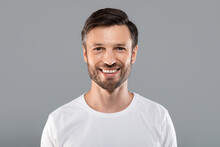 Handsome Young Caucasian Man Smiling At Camera On Grey