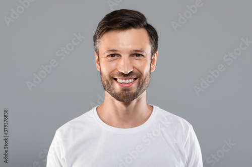 Handsome young caucasian man smiling at camera on grey Tapéta, Fotótapéta