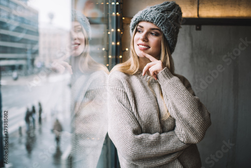 Obraz Contemplative female teenager dressed in stylish winter hat and knitted sweater looking at window and dreaming, happy Caucasian hipster girl 20 years old enjoying recreation and youth lifestyle - fototapety do salonu