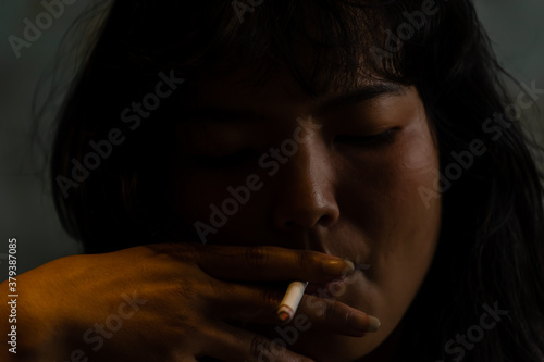 Cuadros en Lienzo A young Asian woman sitting in a cigarette smoking, unconscious