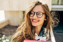 Closeup Portrait Of A Smiling Young Student Woman Wearing Transparent Eyeglasses Standing Next To The College Campus And Carrying Lots Of Books And Folders On A Sunny Day.