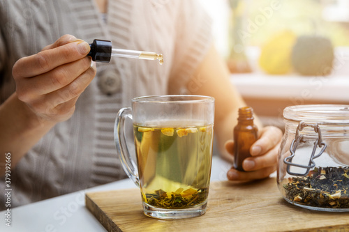 Foto dietary supplements and vitamins - woman adding drop of cbd oil in cup of tea with pipette