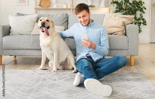 Portrait of young guy with his dog using mobile phone