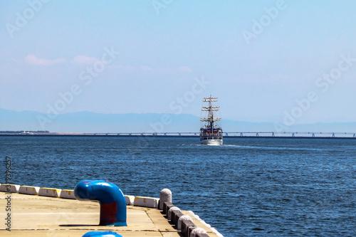 港の埠頭と海に浮かぶ帆船 Wallpaper Mural