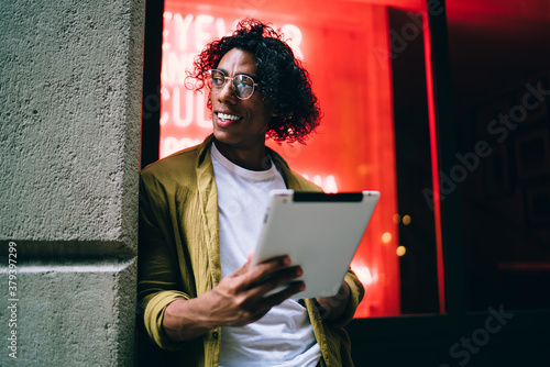 Fototapeta Smiling curly hipster guy in eyewear standing on neon light street with digital tablet share contetnt in vlog,handsome man influencer using touchpad for blogging and share media and multimedia content obraz