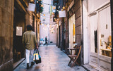 Fototapeta Uliczki - Back view of young trendy dressed hipster guy with bag walking in historical center in evening, rear view 20s of man recreating and strolling on narrow city streets on urban settings in dusk