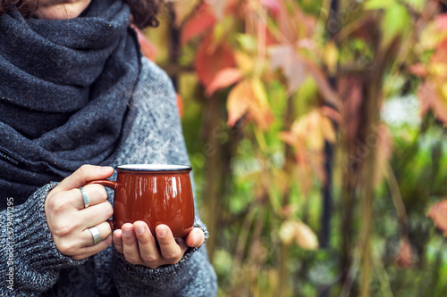 Fotomural Cup of coffee or tea drink in female hands in the autumn park