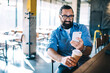 Happy confident mature male entrepreneur in casual wear sitting near bar station in cafe, cheerful hospitable bearded man owner of small business coffee shop checking notification on smartphone
