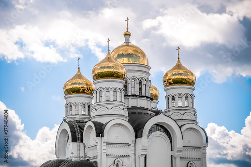 Foto Golden domes, cupolas with Eastern Orthodox crosses on a white Church against a