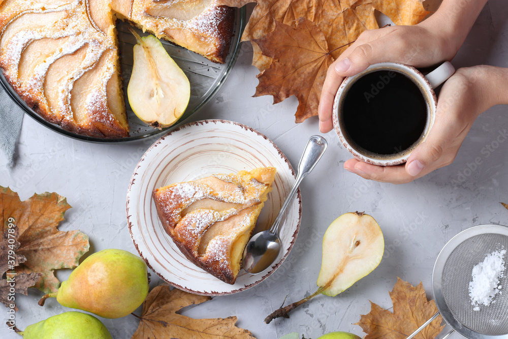 Fototapeta Pie with pears, cup of coffee in female hands and autumn leaves on gray background, top view
