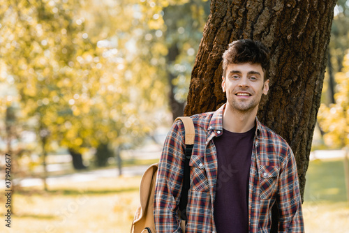 Fototapeta man in checkered shirt looking at camera near tree trunk in park obraz
