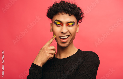 Photographie Gay man with rainbow eyeshadow winking at camera
