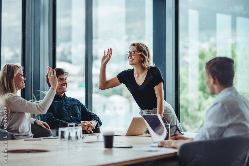Fototapeta Corporate professionals celebrating success in meeting