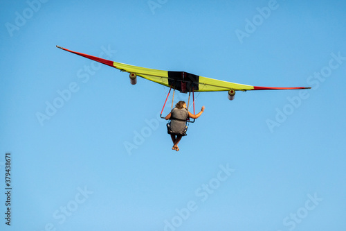 Barefoot girl on a hang glider in the air. Copy space. Canvas Print