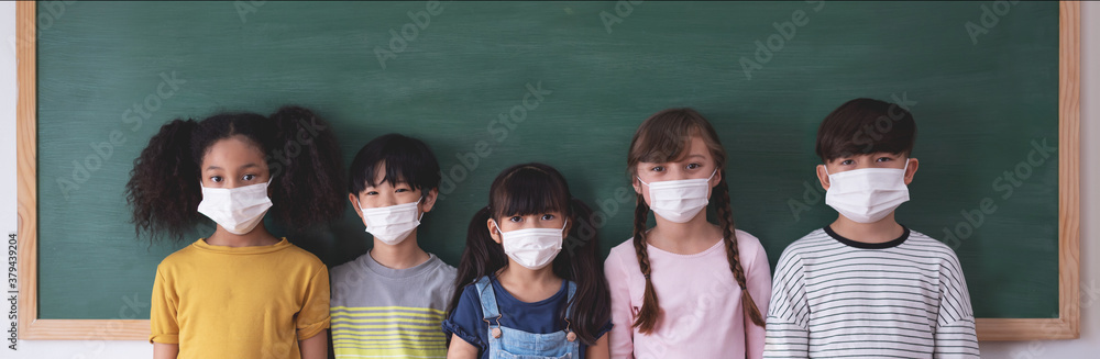 Fototapeta Portrait Of Diversity Elementary School Pupils with protective face mask on blackboard in classroom.