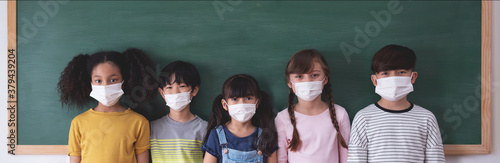 Portrait Of Diversity Elementary School Pupils with protective face mask on blackboard in classroom Wallpaper Mural