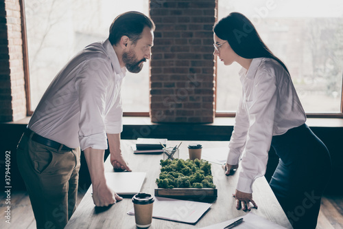 Profile photo of two colleagues have misunderstanding disagreement conflict stand in modern work station place face to face lean hands on table only one boss promotion office indoors