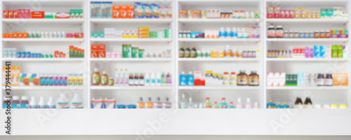 Empty wood counter top with pharmacy drugstore shelves blur pharmaceutical medicine product background