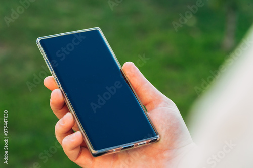 close-up shot of male hands holding smartphone with blank screen copy space for your text message or information content, against green nature background