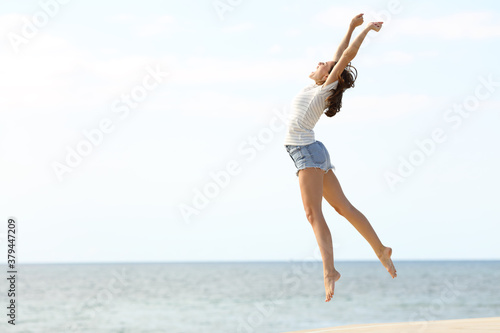Canvastavla Excited woman with long legs jumping on the beach