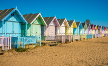 A View Along Brightly Coloured Beach Huts On West Mersea Beach, UK In The Summertime