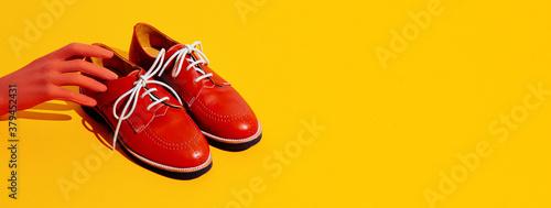 Fototapeta Fake hand and vintage shoes on yellow background. Fashion still life isometric minimal design obraz