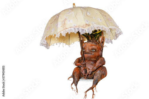 Foto Mandrake root sits hiding under an umbrella, scary, funny, carved from wood