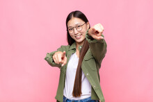 Asian Young Woman Feeling Happy And Confident, Pointing To Camera With Both Hands And Laughing, Choosing You
