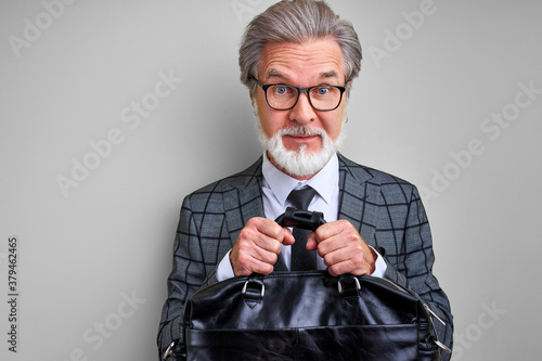 Fotomural greedy senior businessman holding a bag of money, dont's give to someone