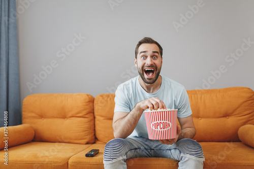 Surprised shocked amazed young bearded man wearing casual blue t-shirt watching movie film, holding bucket of popcorn keeping mouth open sitting on couch resting spending time in living room at home Tapéta, Fotótapéta