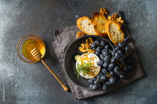 Cuadros en Lienzo Roast camembert and honey with black grapes and baked slice of bread on dark bac