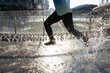 legs and feet of a moving runner, splashing water while the athlete runs over the puddle, details of the lower part and the urban fountain that splashes