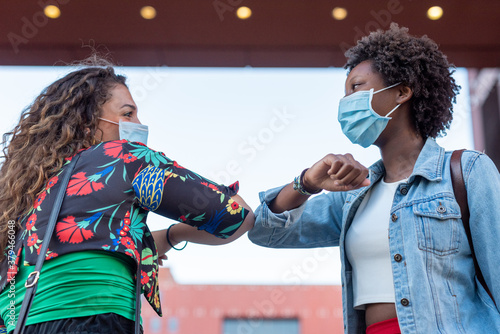 Fototapeta Young african woman and caucasian woman keeping social distance, greeting each other by bumping elbows instead of hugs, kisses or handshaking, wearing mask for prevent coronavirus infection obraz