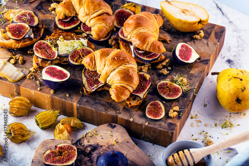 view of delicious freshly baked croissants with figs, pears, nuts and honey © karepa
