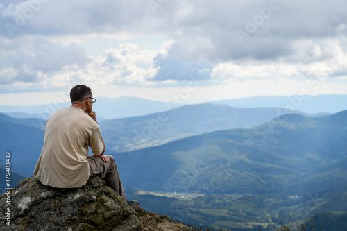 Back view of a man admiring amazing view on top of the mountain Wallpaper Mural