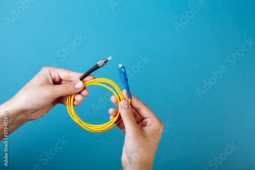 woman's hands hold SC and FC connector fiber optic patch cord single mode on blu Canvas Print