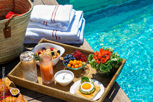 tray with assorted breakfast meal and drinks near swimming pool Canvas Print