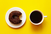 Breakfast Concept. Morning Coffee And Bitten Chocolate Glazed Donut With Sprinkles On A Bright Yellow Background. Baking, Unhealthy Food Concept