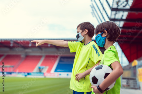 Fotografie, Obraz Two boys wanting to play football in stadium during covid-19