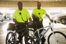 Portrait Of Police Officers With Bicycles Standing In Parking Lot