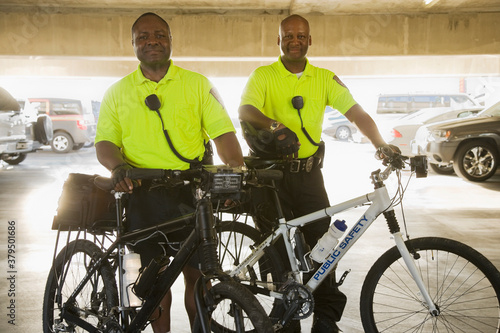 Cuadros en Lienzo Portrait of police officers with bicycles standing in parking lot