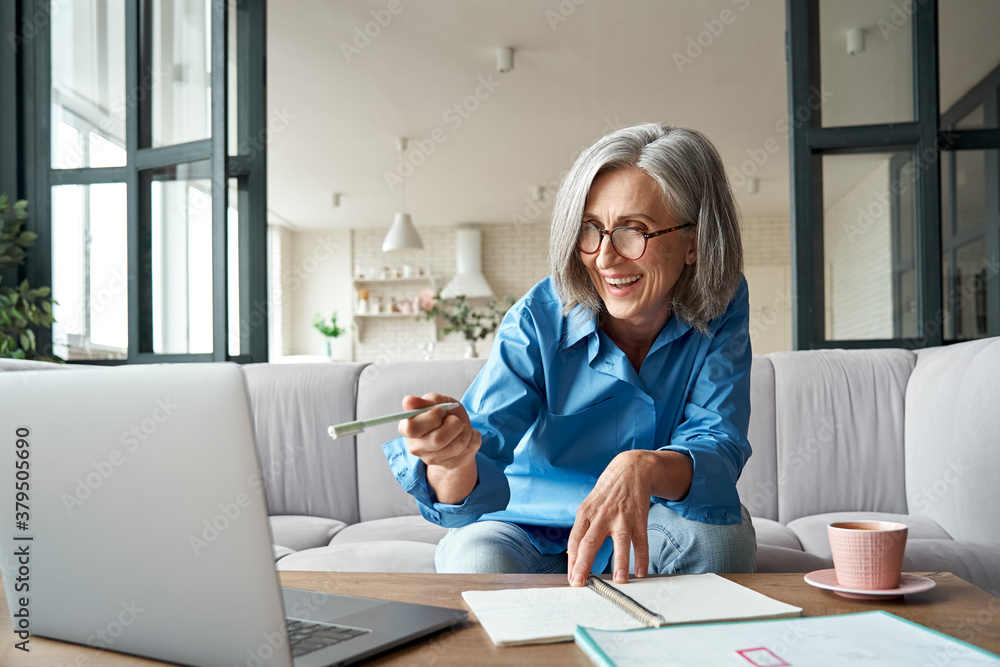 Fototapeta Happy mature older woman video calling on laptop working from home. Smiling 60s middle aged businesswoman talking by conference online virtual chat using computer at home office sitting on couch.