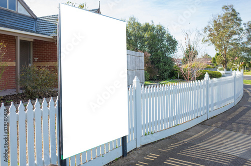 Fotomural Blank white mockup template of a real estate advertisement billboard/sign/board at front of a property/residential house with white wood picket fence in an Australian suburb