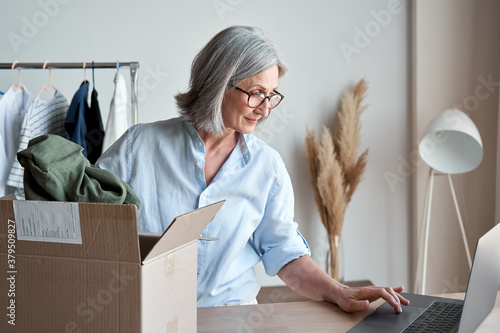 Fotografiet Mature woman fashion designer, dropshipping online clothing store small business owner looking for new e commerce order on laptop preparing packing in postal mail delivery shipping box at workplace