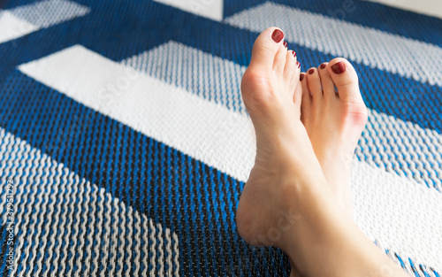 Obraz na plátně Closeup, Bare feet of working woman, resting her toes at home to release pain after long day wearing tight and narrow shoes