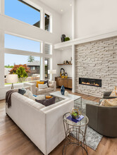 Beautiful Living Room Interior In New Modern Luxury Home With Large Bank Of Windows Showcasing Exterior View. Features Large Stone Fireplace Surround And Roaring Fire.