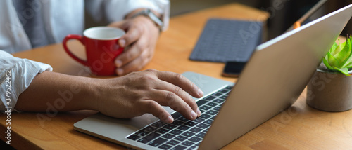 Foto Male hand typing on laptop keyboard and holding coffee cup on wooden table