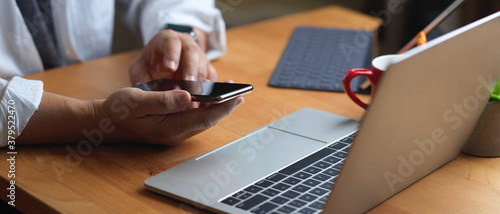 Male hand using smartphone while sitting at worktable with laptop and office sup Wallpaper Mural